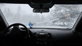 Man som tar bort snö av vindrutan under en snöstorm arkivfilmer