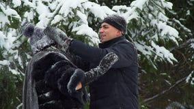 Man som tar bort snö från kläder av kvinnan stock video