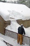 Man som tar bort snö från taket Arkivfoto