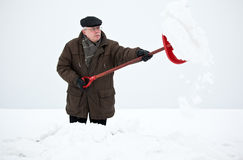 Man som tar bort snow med en skyffel Arkivfoto