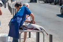 Man som tar bort vågen av en stor fisk i gatan Royaltyfria Bilder