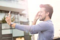 Man som tar en selfie med en smartphone royaltyfri bild