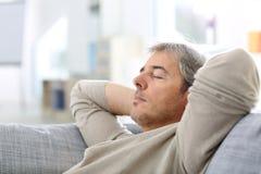 Man som tar en ta sig en tupplur i soffa royaltyfria foton