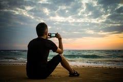 Man som tar foto av solnedgången med mobiltelefonen Arkivfoton