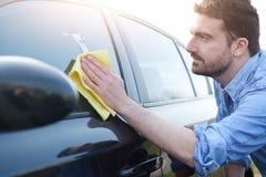Man som tar omsorg och gör ren hans bil royaltyfri foto