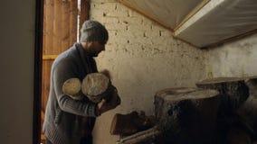 Man som tar trä från gammal ladugård lager videofilmer