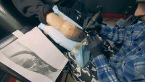 Man som tatuerar en skalle på en bionisk protes, armprotes stock video