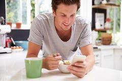 Man som äter frukoststunden som kontrollerar mobiltelefonen Arkivfoto