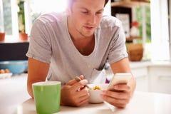 Man som äter frukoststunden som kontrollerar mobiltelefonen Arkivfoton