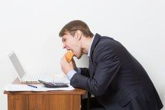 Man som äter hamburgaren på skrivbordet Arkivfoto