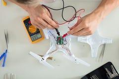 Man som testar den elektriska strömmen av surret genom att använda Multimeterhjälpmedlet royaltyfria bilder