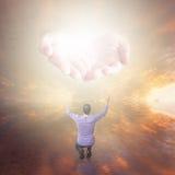 Man som tillber guden Händer med ljust komma från himlen Royaltyfria Bilder