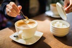 Man som tillfogar socker till hans kaffe arkivbild