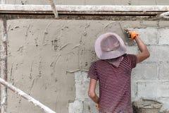 Man som trycker på en cementtegelplatta in i ett lim på en vägg royaltyfri fotografi