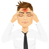 Man som trycker på hans tempel som lider en huvudvärk Arkivbild