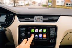 Man som trycker på nu att spela knappen på Apple CarPlay den huvudsakliga skärmen Royaltyfria Foton