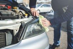 Man som tvättar en bil med en trasa arkivfoton