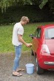 Man som tvättar en liten röd bil Arkivfoton