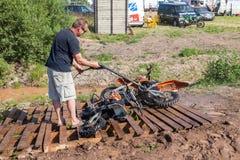 Man som tvättar en loppcykel efter konkurrensen i motocross Royaltyfri Fotografi