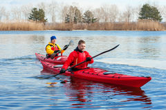 Man som två kayaking på den röda kajaken på floden 02 Arkivbild