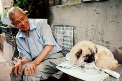 Man som två spelar med en hund utanför deras hem i en traditionell kinesisk stadshutong arkivbild