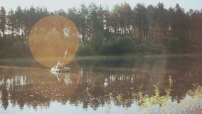 Man som två tillsammans fiskar i uppblåsbart fartyg i morgonen Det härliga landskapet av skogen, sjön och solen rays lager videofilmer