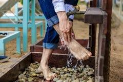 Man som tvättar hans fot på sandstranden Arkivbild