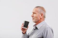 Man som tycker om drycken som isoleras på grå färger fotografering för bildbyråer