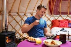 Man som tycker om frukoststunden som campar i traditionella Yurt Arkivfoton