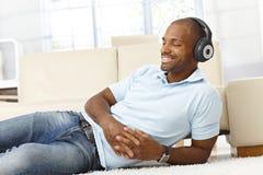 Man som tycker om musik på hörlurar Arkivfoto
