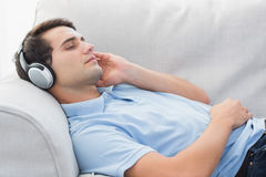Man som tycker om musik som ligger på en soffa Arkivbild