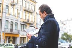 Man som underhåller med tidningen i stad royaltyfria bilder