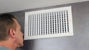 Man som undersöker ett luftlufthål stock video