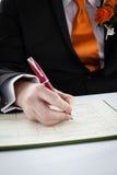 Man som undertecknar ett dokument Arkivbilder