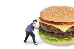 Man som undviker en stor hamburgare Royaltyfri Foto