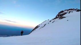 Man som upp klättrar den snöig bergisyxan och isbroddar arkivfilmer
