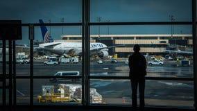 Man som ut ser fönstret på flygplatsen arkivbild