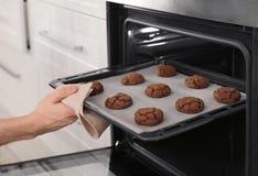 Man som ut tar magasinet av bakade kakor från ugnen i kök fotografering för bildbyråer
