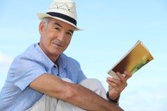 Man som utanför läser en bok royaltyfri fotografi
