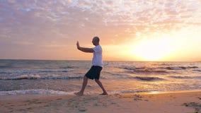 Man som utbildar Taijiquan under morgonsoluppgång i himmel på havsstranden stock video