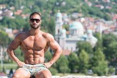 Man som utomhus böjer muskler i sommar Tid Royaltyfria Bilder