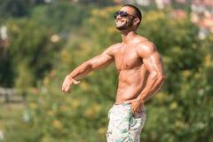 Man som utomhus böjer muskler i sommar Tid Arkivfoton