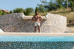 Man som utomhus böjer muskler i sommar Tid Royaltyfri Bild