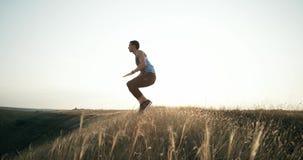 Man som utomhus gör genomkörare för burpeesövningskondition långsam rörelse Hoppa i luften med hans händer som trycker på knä lager videofilmer