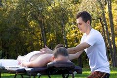 Man som utomhus ger massage till den unga brunetten royaltyfri foto