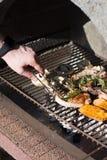 Man som utomhus lagar mat bbq-biffar på galler arkivbilder