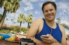 Man som utomhus lyssnar till ståenden för spelare MP3. Arkivbilder