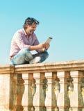 Man som utomhus sitter och använder den digitala minnestavlan Royaltyfri Fotografi