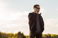 Man som utomhus talar på en Smartphone Royaltyfri Foto