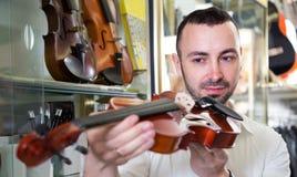 Man som väljer den klassiska fiolen Arkivfoton